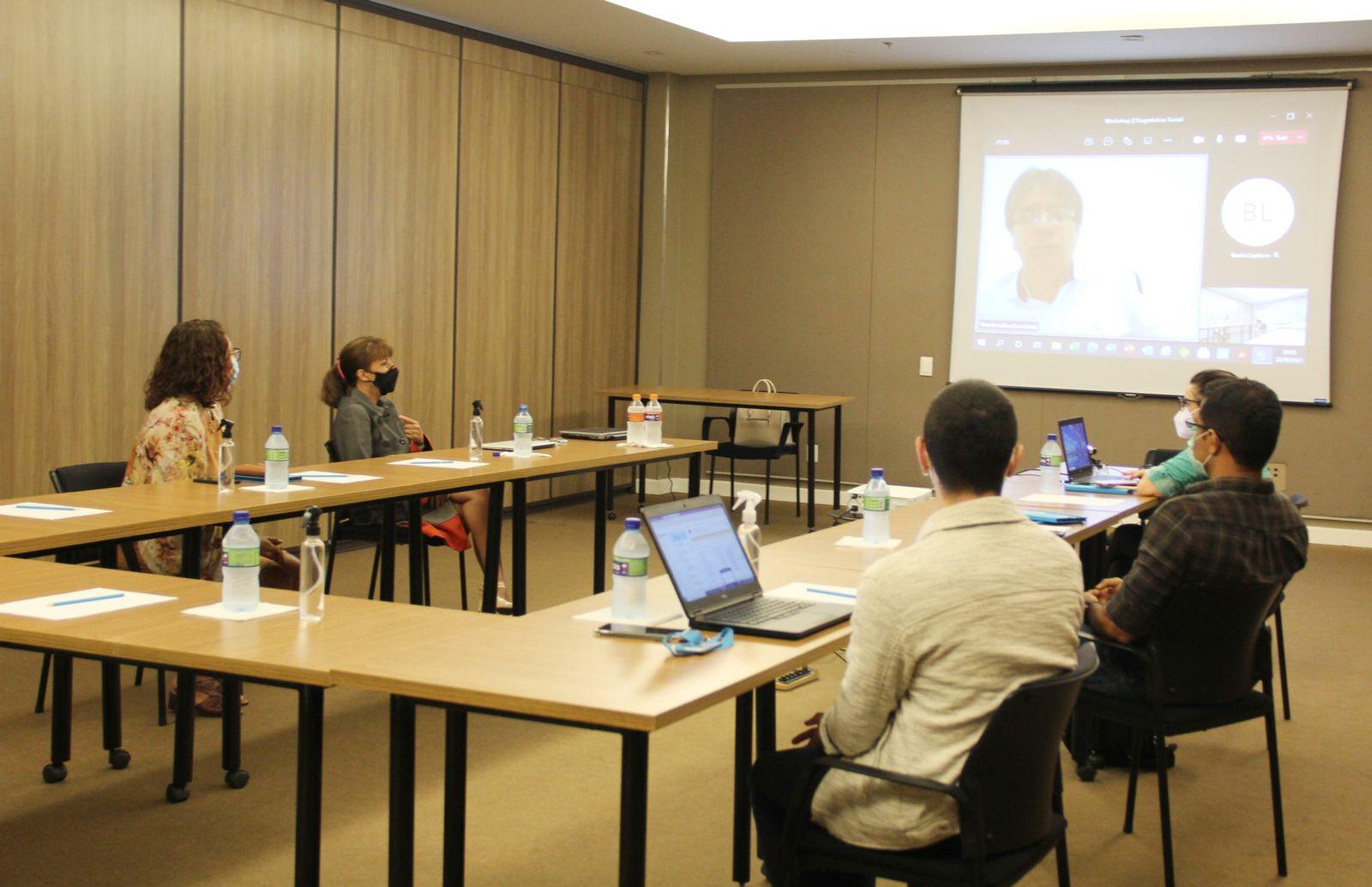 Um grupo de pessoas vê uma apresentação online.