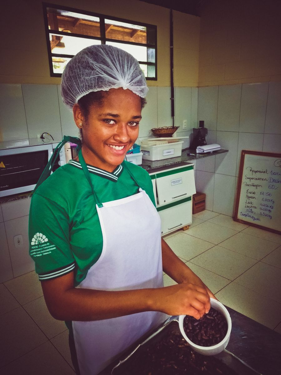 Uma mulher negra jovem sorri enquanto lida com sementes de cacau numa unidade de beneficiamento