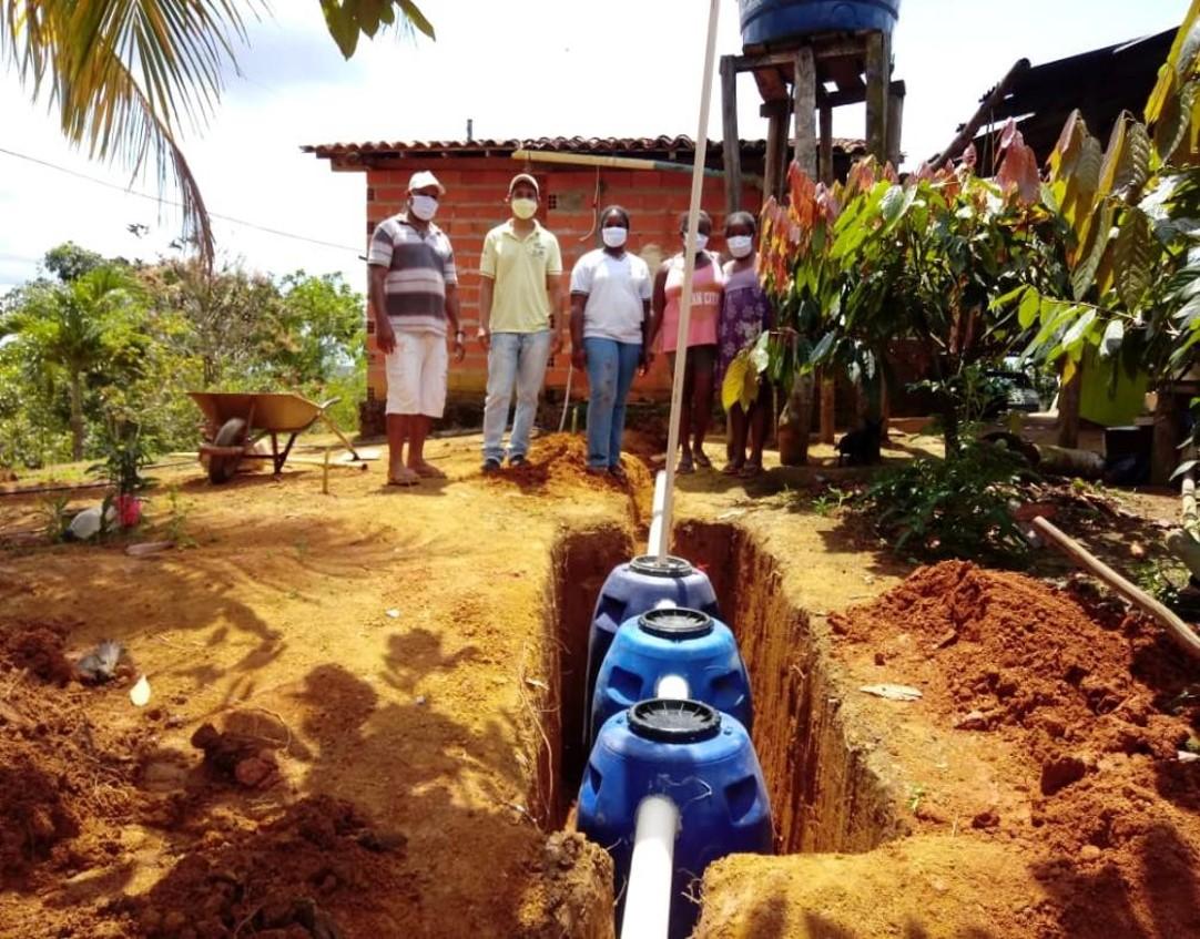 A imagem mostra uma fossa séptica, composta por tanque azuis conectados por um tubo, no chão de uma propriedade rural. Ao fundo há pessoas em pé usando máscara.