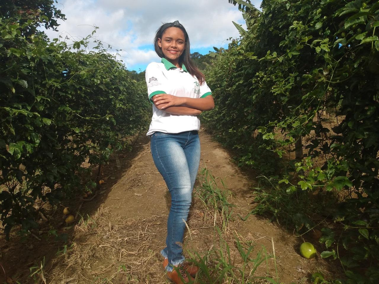 Uma jovem negra está sorrindo confiante, de uniforme escolar, em um cenário rural.