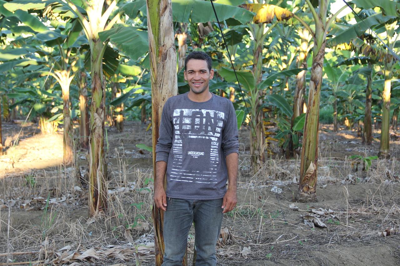 Um homem pardo sorri ao lado de uma plantação de banana.