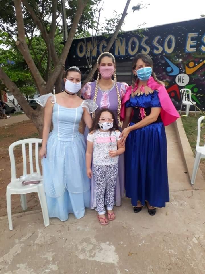 Três mulheres brancas, de máscara, estão vestidas de princesa e abraçam uma menina de máscara.