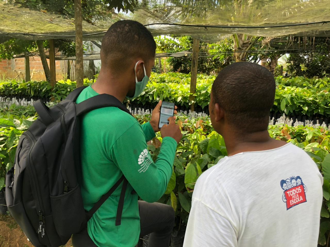 Dois homens olham para um celular num ambiente rural